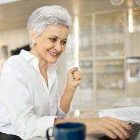successful-mature-female-writer-sitting-desk-wit-e1614063542210