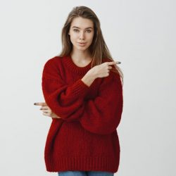 Woman gives us opportunity to chose way in life. Confident feminine european girl in stylish red loose sweater, pointing in different directions, excepting every possibility over gray background.